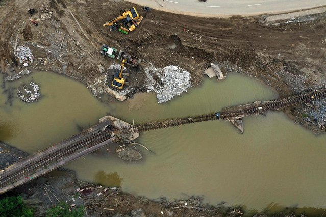 An aerial view shows railroad tracks destroyed by the flood in the wine village Rech near Dernau, Rhineland-Palatinate, western Germany, on August 19, 2021, weeks after heavy rain and floods caused major damage in the Ahr region. (Photo by Ina Fassbender/AFP Photo)