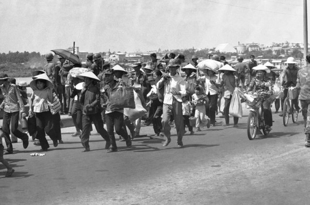 Thousands of Bien Hoa refugees march toward Saigon in Vietnam on Monday, April 28, 1975 to escape a devastating North Vietnamese shelling of their town NW of Saigon. Shelling left town in flamed. (Photo by AP Photo/Franjola)