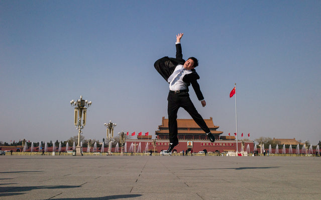 An attendant jumps for a picture during the closing session of the Chinese People's Political Consultative Conference (CPPCC) at the Great Hall of the People in Beijing on March 14, 2016. The CPPCC, a discussion body that is part of the Communist Party-controlled governmental structure, closed on March 14 after its 12-day annual session. (Photo by Fred Dufour/AFP Photo)