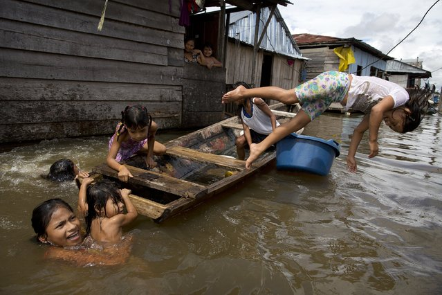 "Children play on a boat in the water outside their homes in the Belen neighborhood of Iquitos, Peru on April 19, 2015. This impoverished Peruvian Amazon community, nicknamed ""Venice of the Jungle"", lives half the year on the water, with canoes replacing motorcycle taxis as the most popular form of transport. (Photo by Rodrigo Abd/AP Photo)"