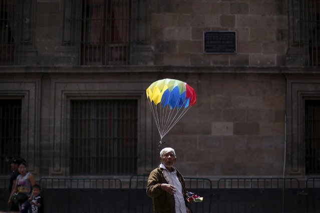 A street vendor stands near a toy tied to a small parachute as it floats along a street in Mexico City March 16, 2016. (Photo by Edgard Garrido/Reuters)