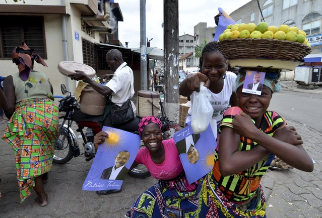 Street vendors hold campaign posters for presidential candidate Patrice Talon ahead of the second round of Benin's presidential election on Sunday in Cotonou, Benin, March 18, 2016. (Photo by Charles Placide Tossou/Reuters)