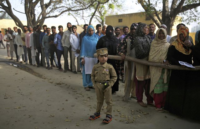 A young boy dressed as a policeman stands as Indians wait in a queue to cast their votes in village Sawaal near Meerut, Uttar Pradesh, India, Thursday, April 11, 2019. India's national elections begins Thursday with millions of voters casting their ballots for 91 of 543 seats in the first phase, choosing their representatives from among 1,300 contestants. Voting is spread over seven days will conclude May 19, and counting will begin May 23. (Photo by Altaf Qadri/AP Photo)