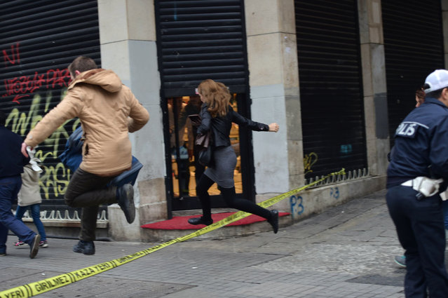 People jump a police line to flee the scene of an explosion on the pedestrian Istiklal avenue in Istanbul on March 19, 2016. Two people, including the bomber, were killed and six others injured in a suicide attack on a major shopping street in Istanbul on Saturday, Turkey's CNN-Turk television reported. (Photo by Bulent Kilic/AFP Photo)