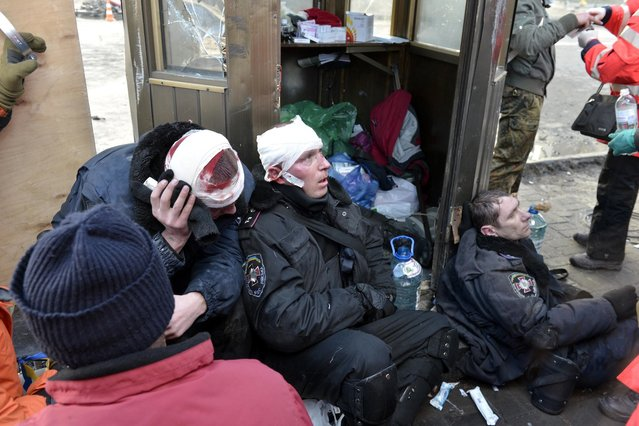 Interior Ministry members injured during clashes with anti-government protesters sit in Kiev, February 18, 2014. (Photo by Reuters/Stringer)