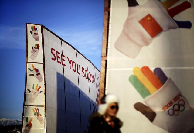 A spectator walks by a sign at the entrance to the Olympic Park ahead of the 2014 Winter Olympics closing ceremony in Sochi. (Photo by David Goldman/Associated Press)