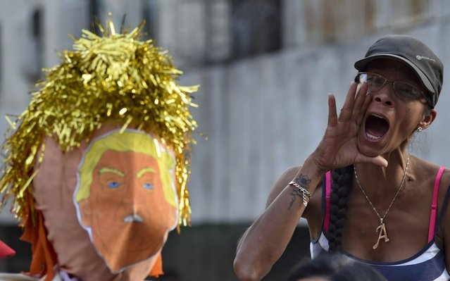"""A supporter of Venezuelan President Nicolas Maduro shouts slogans as a dummy depicting US President Donald Trump is prepared to be burnt, during the traditional """"burning of Judas"""" on Easter Day at Venezuela square, in Caracas, on April 21, 2019. (Photo by Yuri Cortez/AFP Photo)"""