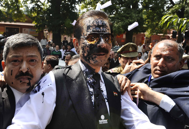 Chairman of Sahara India Pariwar Subrata Roy, his face smeared with ink thrown by a lawyer, walks into the Supreme Court in New Delhi, India, Tuesday, March 4, 2014. A lawyer threw ink at the top Indian businessman as he arrived at India's highest court Tuesday to face charges that his company failed to return billions of dollars to investors. (Photo by AP Photo)