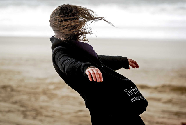 A woman battles the wind during a stormy day at the beach in Scheveningen, The Netherlands, 23 February 2017. (Photo by Remko de Waal/EPA)