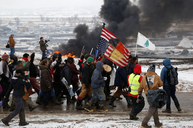 Protesters march, with a structure burning in the background, on the outskirts of the main opposition camp against the Dakota Access oil pipeline near Cannon Ball, North Dakota, U.S., February 22, 2017. (Photo by Terray Sylvester/Reuters)