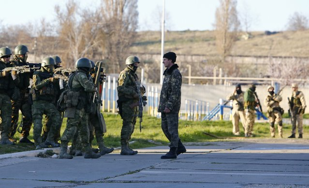 A Ukrainian serviceman (R, front) talks to armed men, believed to be Russian servicemen, who stand guard at a military airbase, in the Crimean town of Belbek near Sevastopol March 22, 2014. (Photo by Shamil Zhumatov/Reuters)