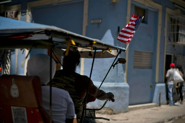 A U.S. flag decorates a man's bike taxi as he cycles through Havana, Cuba, Wednesday, April 17, 2019. (Photo by Ramon Espinosa/AP Photo)
