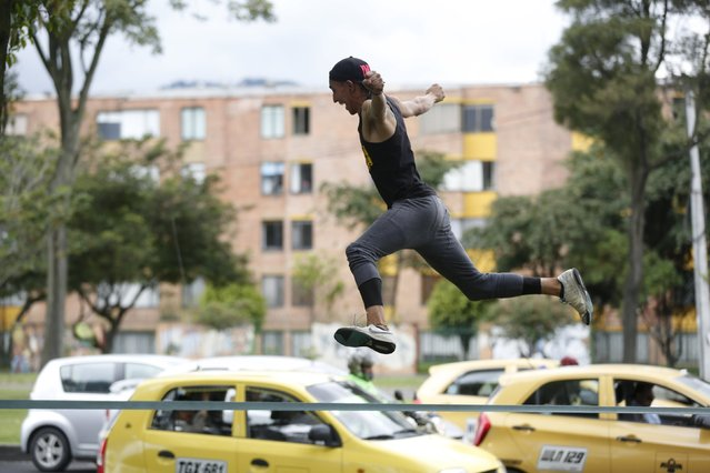 Street performer Mario Manjarres performs on an eslatic rope for tips in front of stopped vehicles at a traffic light in Bogota, Colombia May 23, 2015. (Photo by John Vizcaino/Reuters)