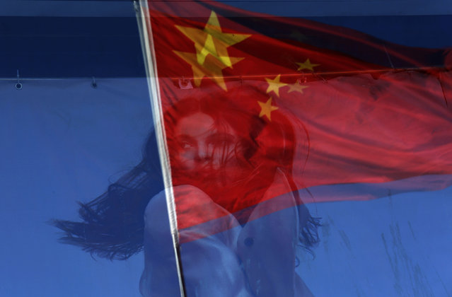 A Chinese national flag is reflected on a fashion poster at a shopping mall in Beijing, China, Tuesday, November 13, 2012. (Photo by Vincent Yu/AP Photo)