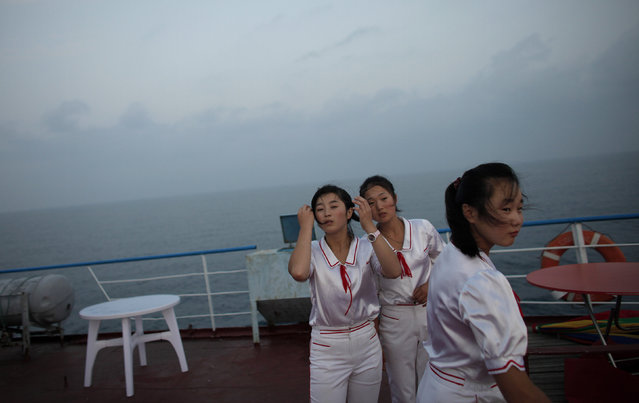 Workers of the Mangyongbyong cruise ship stand on the deck, near Mount Kumgang resort September 1, 2011. (Photo by Carlos Barria/Reuters)