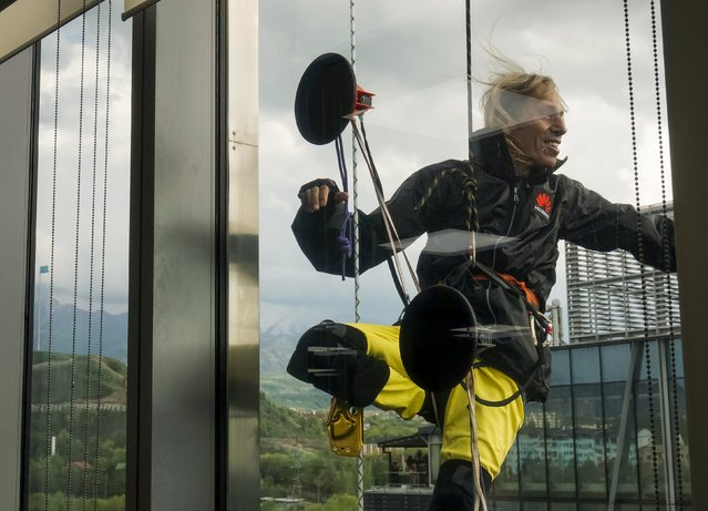 """French climber Alain Robert, also known as """"Spiderman"""", is seen through a window as he scales the 162-metre (531 ft) Esentai Tower in Almaty, Kazakhstan, April 23, 2016. (Photo by Shamil Zhumatov/Reuters)"""