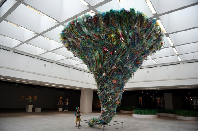 """A boy looks up at the installation entitled """"Tornado by plastic waste"""" by artists from the social enterprise To He at the exhibition """"Plastics Planet"""" in Hanoi on June 27, 2019. (Photo by Nhac Nguyen/AFP Photo)"""
