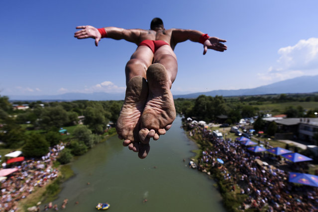"""A man jumps from the 22 meters high bridge """"Ura e Shenjte"""" during the annual traditional High Diving competition near the town of Gjakova on July 22, 2019. (Photo by Armend Nimani/AFP Photo)"""