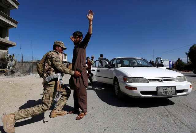 An Afghan policeman inspects passengers at a checkpoint on the outskirts of Jalalabad province, Afghanistan, April 29, 2016. (Photo by Reuters/Parwiz)