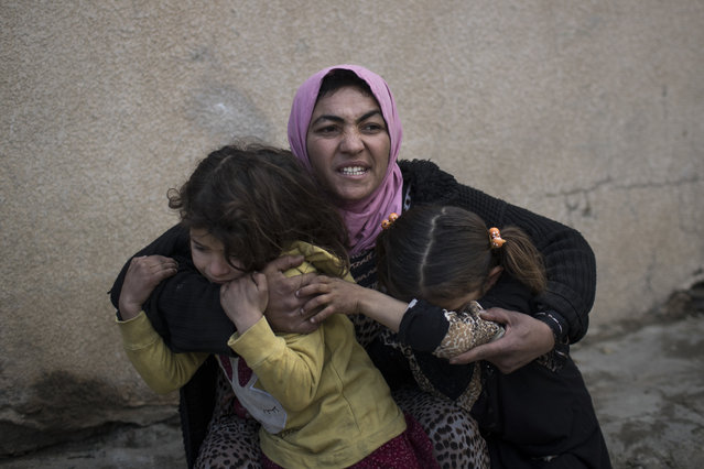 In this Tuesday, March 14, 2017 file photo, A woman holds her daughters as gunshots are heard in a neighborhood recently liberated by Iraqi security forces in western Mosul, Iraq. (Photo by Felipe Dana/AP Photo)