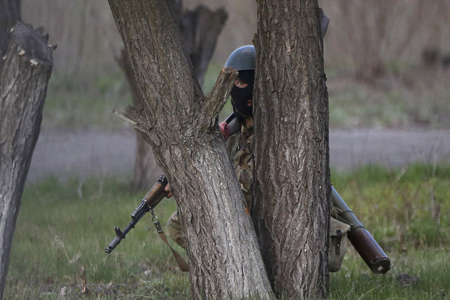 """An Ukrainian soldier takes cover behind a tree as pro-Russia protesters gathered in front of a Ukrainian airbase in Kramatorsk, in eastern Ukraine April 15, 2014. Ukrainian armed forces on Tuesday launched a """"special operation"""" against militiamen in the country's Russian speaking east, authorities said, recapturing a military airfield from pro-Moscow separatists. (Photo by Marko Djurica/Reuters)"""