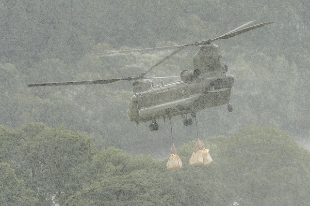 A RAF CH-47 Chinook helicopter carries sandbags to Whaley Bridge dam in Derbyshire, England on August 6, 2019 to carry out major emergency repairs after the recent heavy flood waters caused a partial collapse of the dam head. (Photo by News Images/Rex Features/Shutterstock)