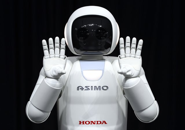 Honda North America shows off their new Asimo Robot along with their new Honda FIT to the media during the second press preview day at the 2014 New York International Auto Show  April 17, 2014  in New York at the Jacob Javits Center. (Photo by Timothy A. Clary/AFP Photo)
