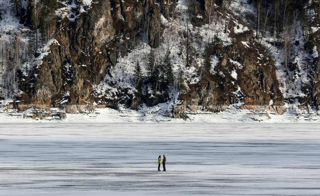 A couple talks on spring ice of the frozen Yenisei River outside Krasnoyarsk, Russia March 18, 2019. (Photo by Ilya Naymushin/Reuters)
