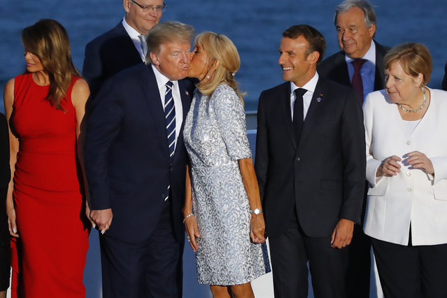 French President Emmanuel Macron, second right, and German Chancellor Angela Merkel watch Brigitte Macron kissing U.S President Donald Trump while first lady Melania Trump, left, looks away, during the G7 family photo Sunday, August 25, 2019 in Biarritz. A top Iranian official paid an unannounced visit Sunday to the G-7 summit and headed straight to the buildings where leaders of the world's major democracies have been debating how to handle the country's nuclear ambitions. (Photo by Francois Mori/AP Photo)