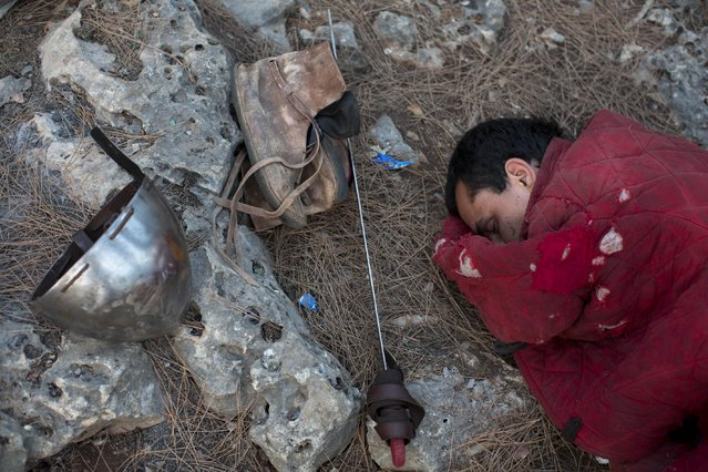 In this Saturday, July 4, 2015 photo, an Israeli member of a knight club sleeps before the reenactment of the Battle of Hattin in Lavi Forest, northern Israel. (Photo by Oded Balilty/AP Photo)
