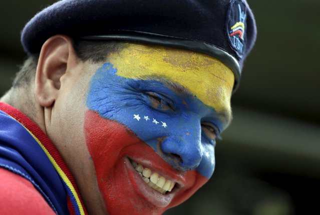 A man with the colors of the Venezuelan flag on his face, smiles after taking part in a military parade to celebrate the anniversary of Venezuela's independence in Caracas, July 5, 2015. (Photo by Jorge Dan Lopez/Reuters)