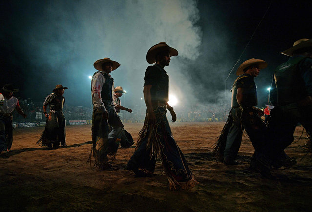Riders walk out before competing at a rodeo event in Monte Negro, south of the Amazon basin, Rondonia state, Brazil on August 30, 2019. In recent years, Monte Negro has expanded as a key cattle town with a strong cowboy culture. (Photo by Carl De Souza/AFP Photo)