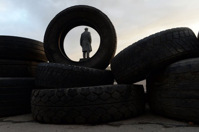 A statue of Soviet leader Vladimir Lenin, visible through a tire, stands on the square outside a regional administration building seized by pro-Russian separatists in the eastern Ukrainian city of Slavyansk on April 30, 2014. (Photo by Vasily Maximov/AFP Photo)