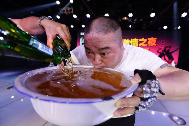 A singer drinks from a huge bowl of beer on-stage as he pays tribute to the customers after performing at an entertainment club in Beijing, on May 8, 2014. (Photo by Jason Lee/Reuters)