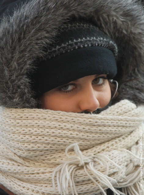 A young woman walks bundled against the cold