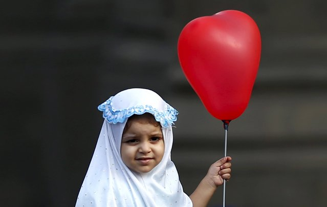 A Muslim girl holds a ballon after Eid-al-Fitr prayers in the old Islamic area of Cairo, Egypt, July 17, 2015. (Photo by Amr Abdallah Dalsh/Reuters)