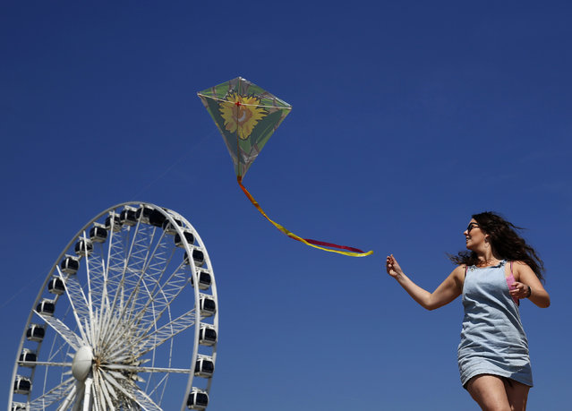 Outreach worker, Kathryn Owen plays with a kite in the sunny weather on Brighton beach in southern England May 16, 2014. (Photo by Luke MacGregor/Reuters)
