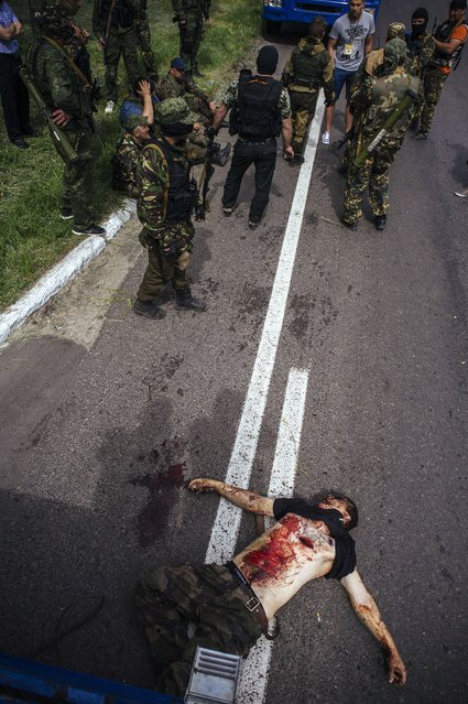 Pro-Russian gunmen stand next to a dead body at a checkpoint outside of the eastern Ukrainian city of Donetsk, on May 23, 2014. At least five people were killed in fighting early Friday between pro-Russian militiamen and Ukrainian forces near the eastern city of Donetsk, an AFP photographer said. Fighting in the east has seen a bloody resurgence ahead of Sunday's presidential election that the pro-Russian insurgents have vowed to disrupt. (Photo by Dimitar Dilkoff/AFP Photo)