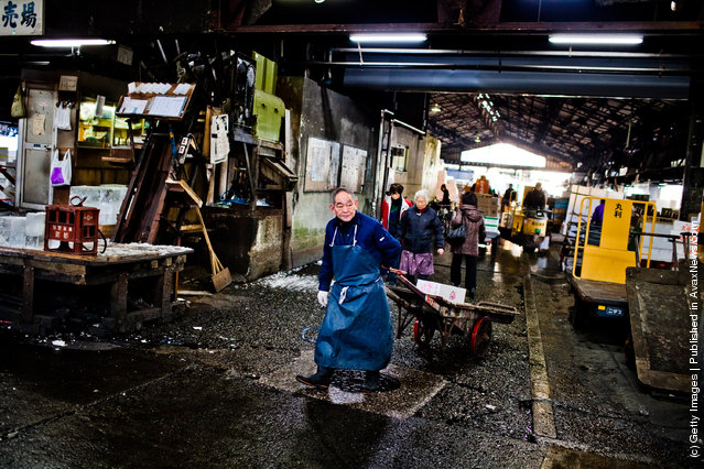 A workers wheels boxes used to store fish and other seafood goods, which will then be packed with ice at the Tsukiji fish market