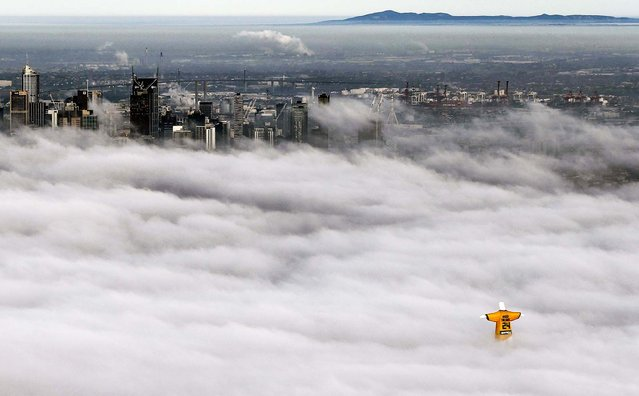 A hot-air balloon in the likeness of Brazil's Christ The Redeemer statute, wearing the colors of Australia's soccer team, floats through clouds over the Melbourne skyline, June 10, 2014. (Photo by Dave Callow/sportsbet.com.au)