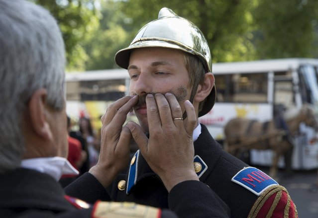 A Belarussian firefighter sticks an artificial moustache on his colleague before a parade of historic and modern fire equipment, during a celebration to mark their profession in central Minsk July 25, 2015. (Photo by Vasily Fedosenko/Reuters)