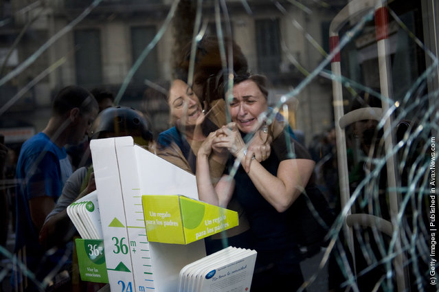 A woman comforts her fellow worker after demonstrators smashed a shop window during heavy clashes with riot police during a 24-hour strike on March 29, 2012 in Barcelona, Spain
