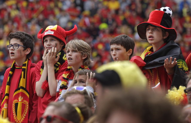 Young fans of the Belgian national soccer team react after Algeria scored with a penalty, as they watch the match broadcast live on a giant video screen at the Ghelamco soccer stadium in Ghent, western Belgium, Tuesday, June 17, 2014. Belgium plays against Algeria, South Korea and Russia in Group H of the World Cup 2014 in Brazil. (Photo by Yves Logghe/AP Photo)