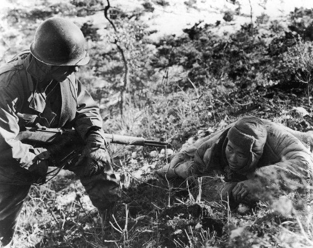 An American soldier taking a communist prisoner during the Korean war, 1952