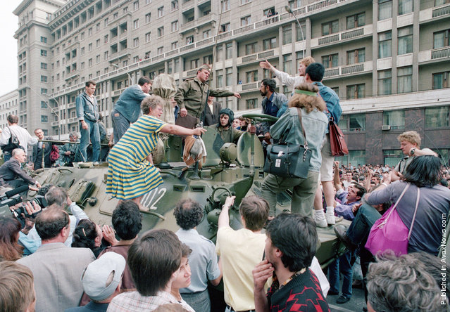 A crowd gathers around a personnel carrier as some people climb aboard the vehicle and try to block its advance near Red Square in downtown Moscow, on August 19, 1991. Military vehicles were on the streets of Moscow following the announcement that Soviet President Mikhail Gorbachev was replaced by Gennady I. Yanayev in a coup attempt by hard-line Communists