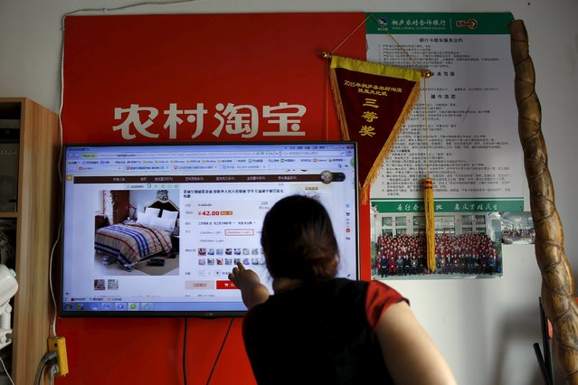 A customer points at a screen displaying a website of Alibaba's Taobao at a rural service centre in Yuzhao Village, Tonglu, Zhejiang province, China, July 20, 2015. (Photo by Aly Song/Reuters)
