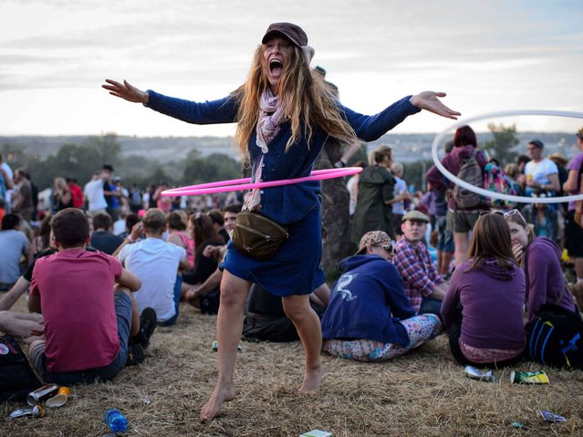 A festival goer uses a hula hoop, as revelers gather ahead of this weekends Glastonbury Festival of Music and Performing Arts on Worthy Farm in Somerset. (Photo by Leon Neal/AFP Photo)