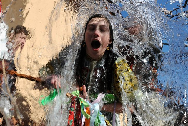 Young Slovaks dressed in traditional costumes throw a bucket of water at a girl as part of Easter celebrations in the village of Trencianska Tepla, Slovakia, April 9, 2012. Slovakia's men splash women with water to symbolize youth, strength and beauty for the upcoming spring season