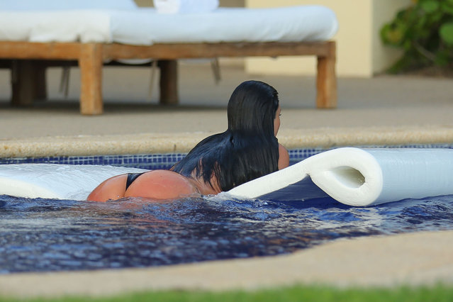Kim Kardashian, wearing a skimpy black bikini, takes a plunge in the pool as she enjoys a second honeymoon in Mexico with Kanye West. The newly-weds stayed at the exclusive home of Girls Gone Wild founder Joe Francis, after jetting in to Punta Mita, to catch some pool side relaxation - and celebrate Kanye's 37th birthday. The Wests honeymooned in Ireland and Prague after their May 24 wedding in Italy. Photos June 15,2014. (Photo by Brian Prahl/Splash News)