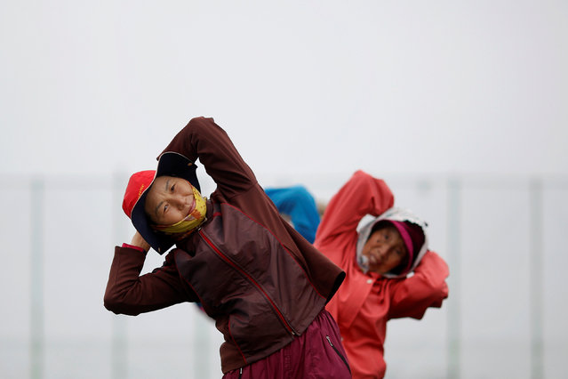 Elderly residents exercise on the island of Yeonpyeong, which lies in the Yellow Sea, South Korea, April 9, 2014. (Photo by Damir Sagolj/Reuters)